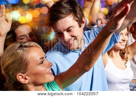party, holidays, music, nightlife and people concept - happy couple having fun and waving hands at concert in night club