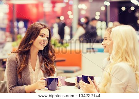drinks, communication, friendship and people concept - happy young women with coffee cups sitting at table and talking in mall or cafe