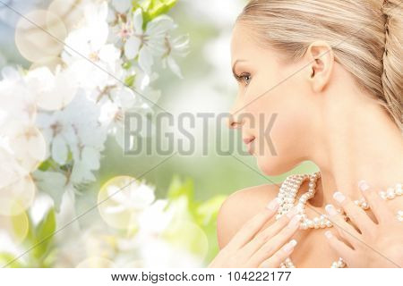 beauty, luxury, people, holidays and jewelry concept - beautiful woman with sea pearl necklace or beads over cherry blossom background
