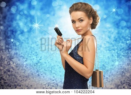 people, luxury, holidays and finance concept - beautiful woman in evening dress with vip card and handbag over blue lights background