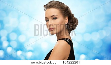 people, holidays, jewelry and glamour concept - beautiful woman in evening dress wearing earrings over blue lights background