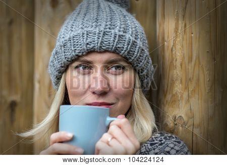 Beautiful blonde female drink coffee uoutdoor