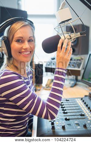 Portrait of happy female radio host broadcasting in studio