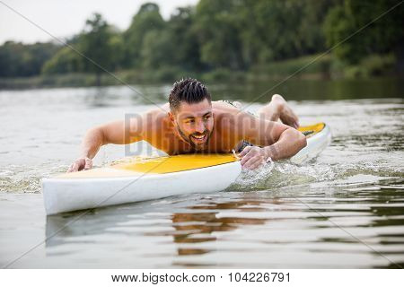 Athletic Man Swimming On A Paddleboard