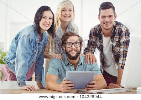 Portrait of smiling business people using digital tablet at desk in office