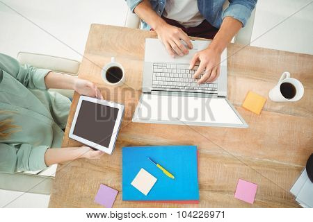 Overhead view of man and woman holding digital tablet while sitting at desk