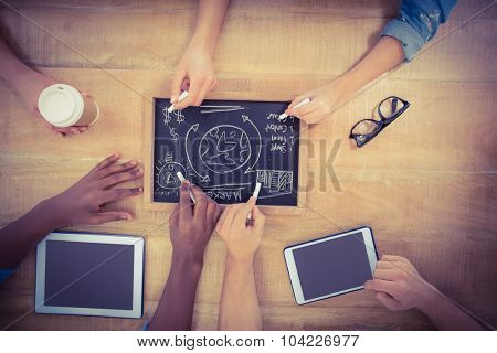 Overhead view of cropped hands writing business terms on slate with person touching digital tablet at table