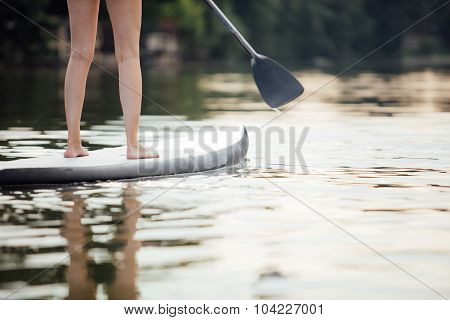 Clouse-up Of A Woman Legs On Paddleboard