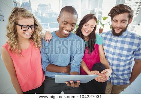 Smiling business people using digital tablet in creative office
