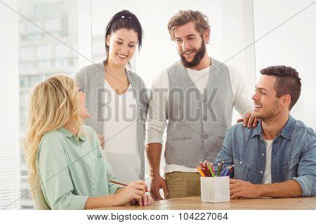 Smiling business people talking at desk
