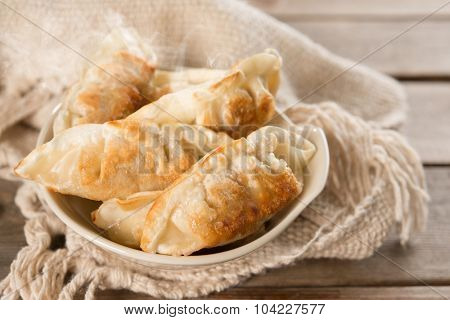 Fresh pan fried dumplings on bowl with hot steams. Asian dish on rustic vintage wooden background.