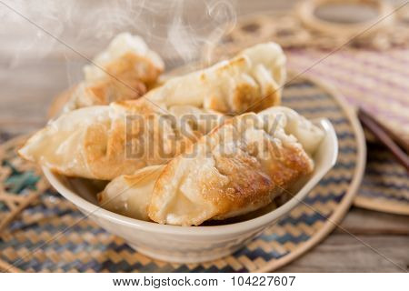 Fresh pan fried dumplings on bowl with hot steams. Asian cuisine on rustic vintage wooden background.