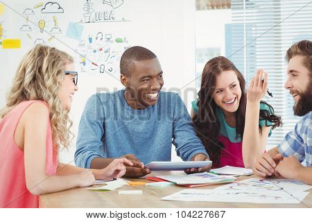 Happy business professionals using digital tablet at desk in creative office