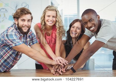 Portrait of smiling business team putting their hands together at desk