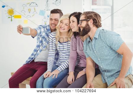 Smiling business people taking self portrait on smartphone while sitting on desk in office