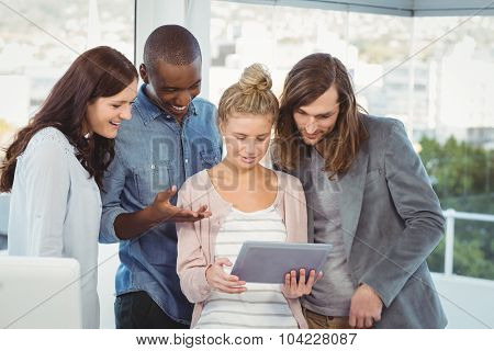 Smiling woman holding digital tablet and discussing with coworkers at creative office