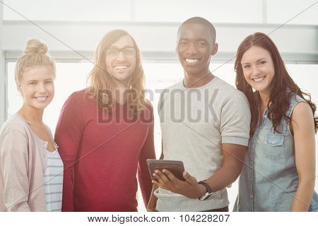Portrait of smiling man holding digital tablet while standing with coworkers at office