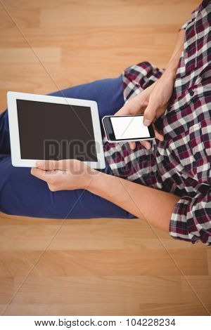 Mid section of hipster using smartphone while holding digital tablet