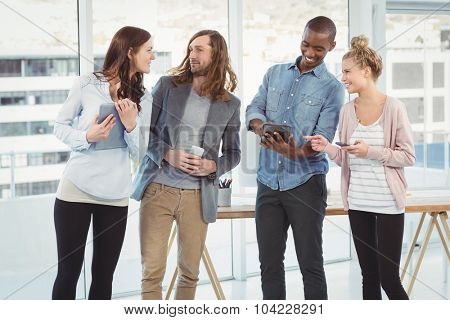Business team using technology while standing at creative office