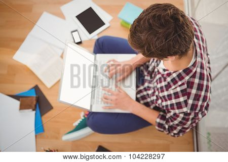 High angle view of creative businessman working on laptop while sitting on hardwood floor