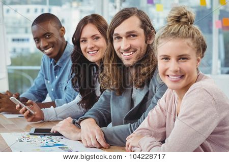 Portrait of smiling business people at desk in office