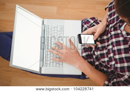 Cropped image of hipster sitting with laptop on top using smartphone in office