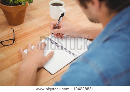 Cropped image of hipster writing on spiral book at desk in office