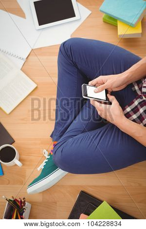 Cropped image of hipster using smartphone while sitting on hardwood floor in office