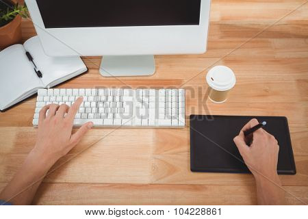 Cropped image of man using graphics tablet while typing on keyboard at desk in office