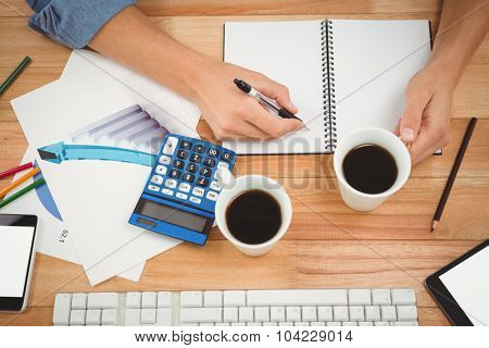 Cropped hand of hipster holding coffee while writing on spiral notebook at table in office
