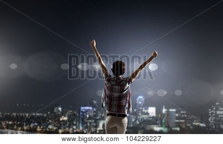 Rear view of young woman with hands up looking at night city
