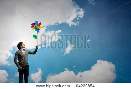 Young happy guy in casual with colorful windmill in hand