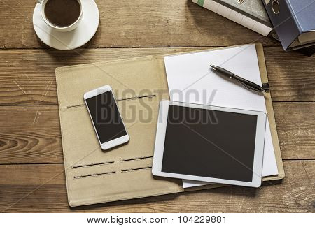 empty tablet and phone lying on an office folder