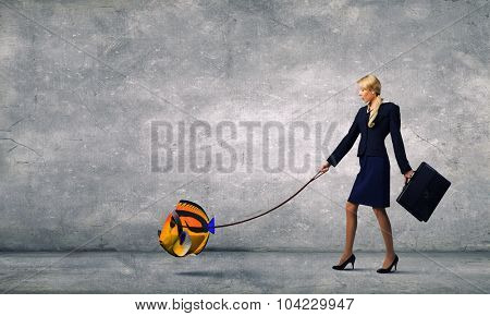 Young businesswoman walking with big exotic fish on lead