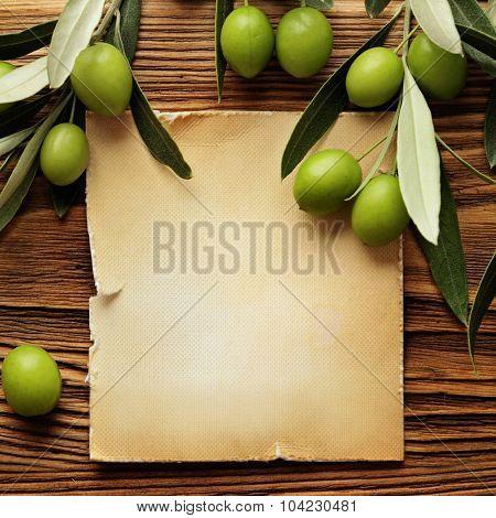 Olives over wooden background and olive oil label