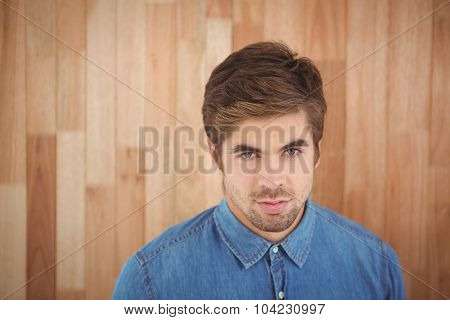 Portrait of confident businessman against wooden wall