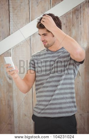 Happy man using smartphone against wooden wall