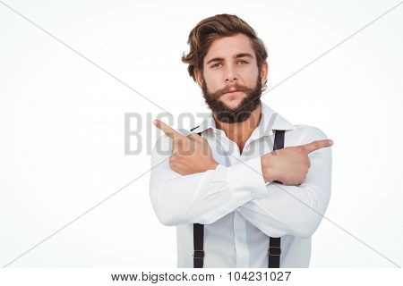 Portrait of confident hipster pointing sideways with arms crossed against white background
