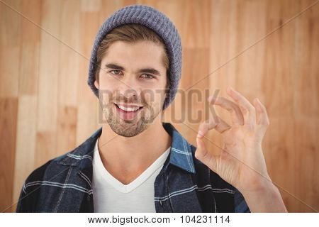 Portrait of happy hipster showing OK sign against wooden wall in office