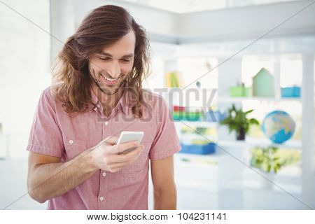 Hipster smiling while looking at mobile phone in office