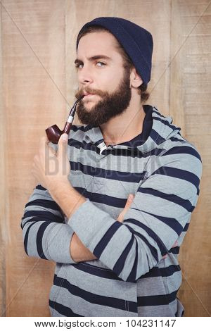 Portrait of serious hipster smoking pipe against wooden wall