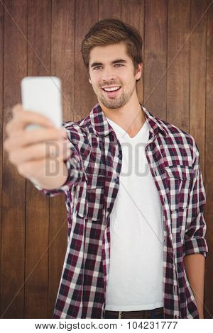 Happy hipster taking selfie while standing against wooden wall
