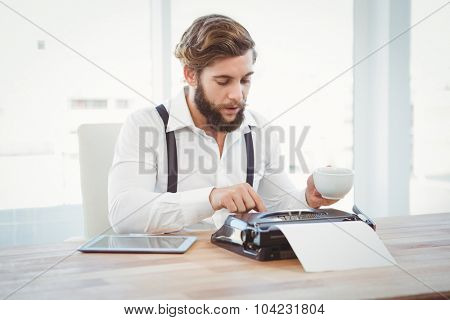 Hipster holding coffee working on typewriter at desk in office