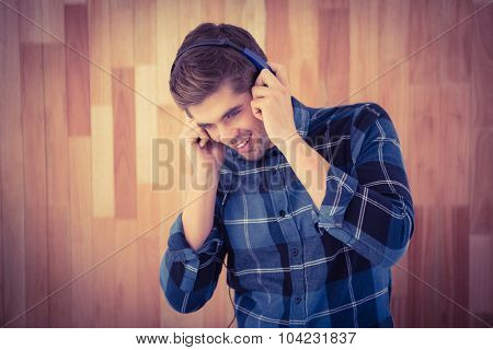 Hipster smiling while wearing headphones against wooden wall