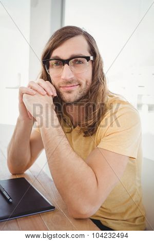 Portrait of confident hipster at desk in office
