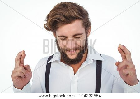 Hipster with fingers crossed against white background