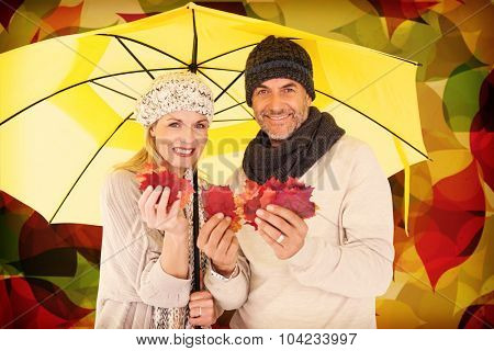 Portrait of couple holding autumn leaves while standing under yellow umbrella against autumnal leaf pattern in warm tones