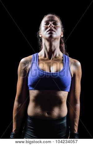 Fit woman meditating while standing against black background