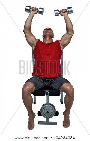 Healthy man lifting dumbbells while sitting on bench press against white background
