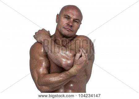 Portrait of bodybuilder stretching with hands against white background